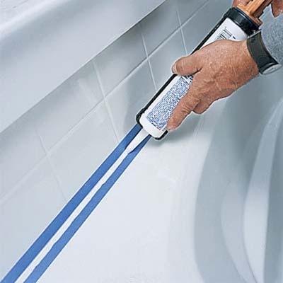 man caulking bathroom tile