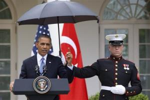 President Barack Obama speaks under an umbrella held by a Marine as a light rain falls during a news conference with Turkish Prime Minister Recep Tayyip Erdogan.