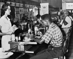 In this Sept. 14, 1960, photo, an unidentified black man eats at a lunch counter in Tampa, Fla., during a citywide protest against segregation.