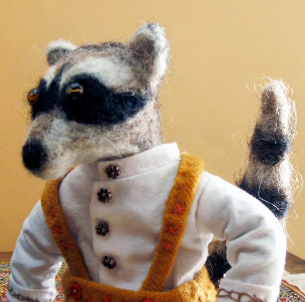 Racoon - handmade animal doll - grey and black needlefelted wool, yellow embroidered lederhosen, white shirt, buttons.