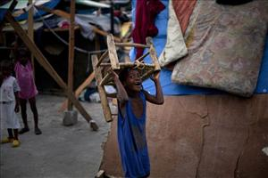 A child carries a chair in a street in Port-au-Prince, Thursday, Feb. 11, 2010. A powerful earthquake hit Haiti on Jan. 12.