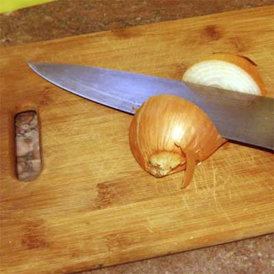 cutting board with knife resting between two halves of an onion
