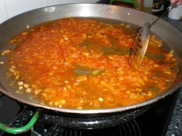 Freír el tomate con la cebolla