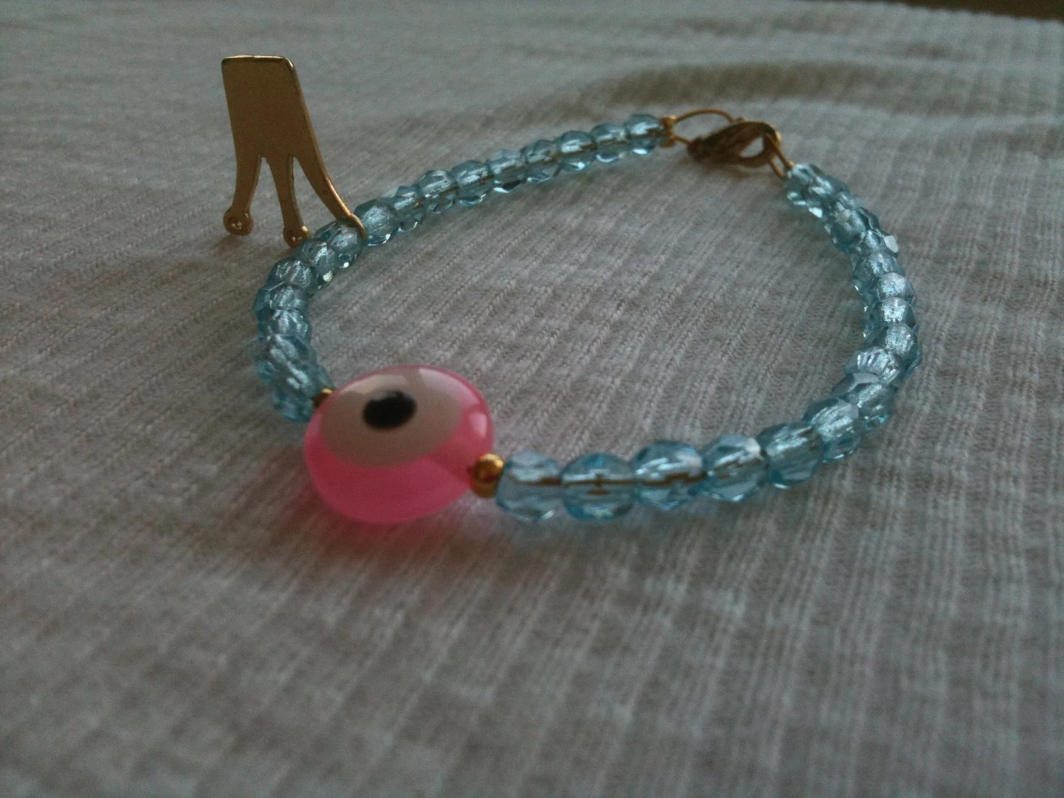 Beaded bracelet in Aquamarine with an Evil eye and a crown Charm