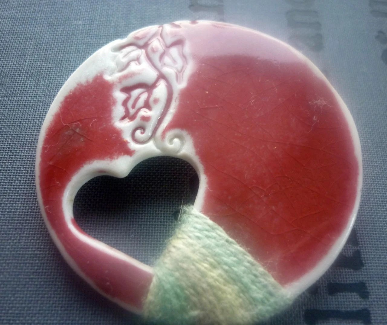 Ceramic Brooch: Porcelain impressed with ivy leaves, heart cut out in Peach Bloom Red glaze, with green silk thread.