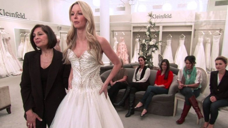 a consultant and a bride look at a dress with the bride's entourage in the back