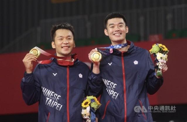 東京奧運羽球男子雙打金牌戰31日晚間進行,台灣好手李洋(左)、王齊麟(右)擊敗中國組合劉雨辰與李俊慧,成功為台灣拿下奧運羽球史上首金,兩人開心秀出獎牌,笑得燦爛。中央社記者吳家昇攝 110年7月31日