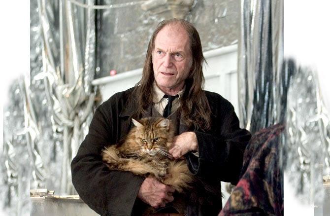 Fotka Arguse Filche z vánočního plesu. Filch má oblek a v náruči drží Paní Norrisovou.