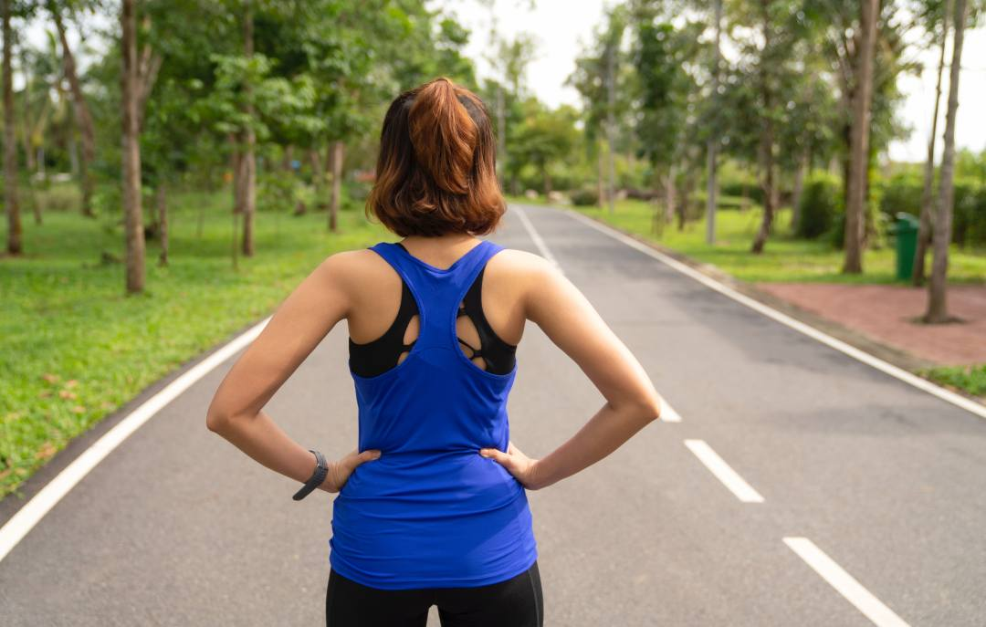 A woman stares down a road, preparing to run. Working out while you're high on cannabis affects your body in these ways.