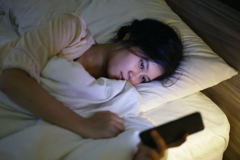 indonesia girl using cell phone in bed