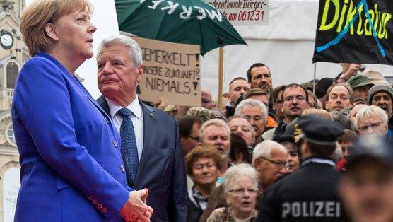 Merkel und Gauck von Demonstranten übel beschimpft (Bild: AFP/ODD ANDERSEN, AP/Jens Meyer)