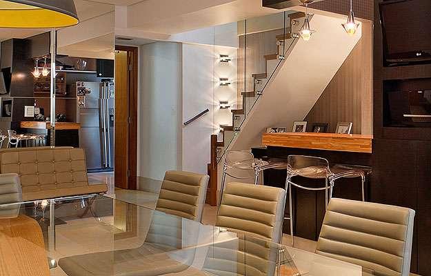O guarda-corpo da escada em vidro prolonga o olhar e aumenta a sala (Henrique Queiroga/Divulgação)