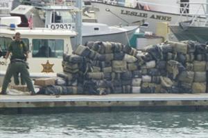 Policiais recolhem droga apreendida no mar