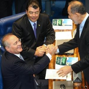 Senadores Renan Calheiros (PMDB-AL), Eduardo Braga (PMDB-AM; sentados) e Inácio Arruda (PCdoB-CE) se cumprimentam no plenário durante sessão que elegeu Calheiros presidente da Casa novamente