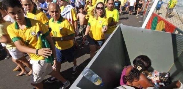 19.jun.2013 - Imagem mostra mulher dentro de lixo sendo ignorada por torcedores a caminho do jogo Brasil x México, no estádio Castelão, em Fortaleza (CE). 'Esse é o legado da Copa das Condeferações', disse o fotógrafo que registrou a cena