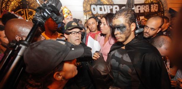 "Manifestante tira máscara e mostra documento a policial militar durante o ""Baile dos Mascarados"" nas escadarias da Câmara Municipal do Rio"