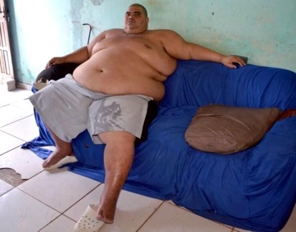 Alex Rodrigues dos Santos, 38 anos, só vai do sofá para a cama e para o banheiro por causa das limitações causadas por seu peso. Ele tenta cirurgia no SUS, mas está na fila