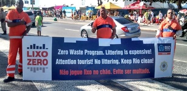 Fiscais da Comlurb exibem faixa em inglês para orientar turistas estrangeiros sobre o programa Lixo Zero