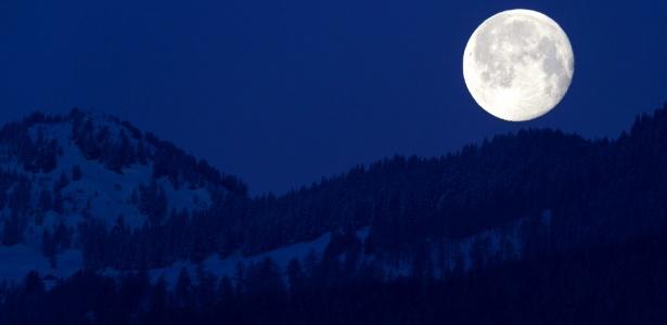 Lua cheia aparece atrás dos Alpes Suíços, vista de Charrat, no sul do país