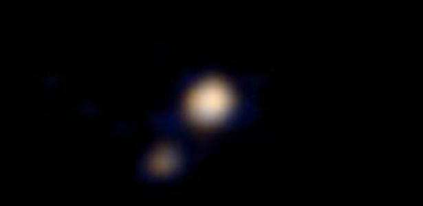 A Nasa (Agência Espacial Americana) publicou nesta quarta-feira (15) a primeira imagem em cores de Plutão e sua lua maior, Caronte, obtida pela sonda New Horizons, que deve chegar ao planeta anão no mês de julho