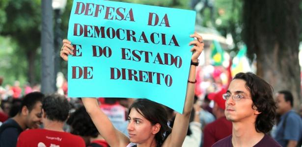 """Manifestante segura cartaz com """"defesa da democracia e do Estado de direito"""""""
