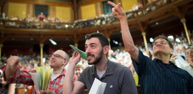 Alex Frieden (c) e colegas jogam aviões de papel durante a cerimônia do 25º IgNobel, na Universidade de Harvard, nos Estados Unidos