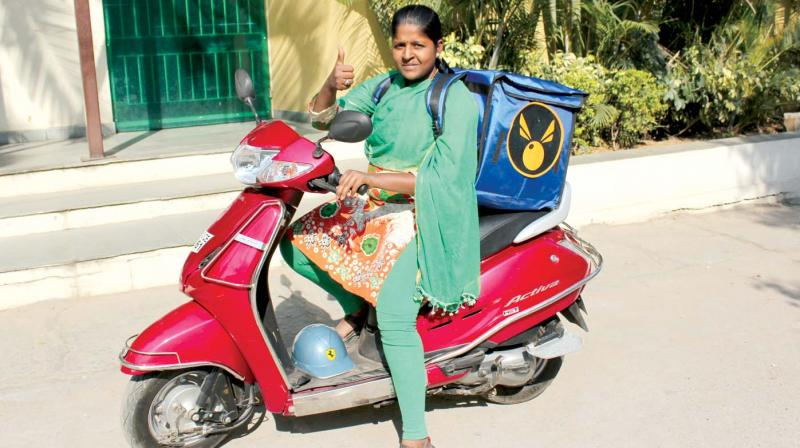 A woman on a scooter delivering something that could be menstrual products (....but probably is not.)  From https://www.deccanchronicle.com.