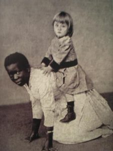 young black girl on her hands and knees with a white child riding her back.