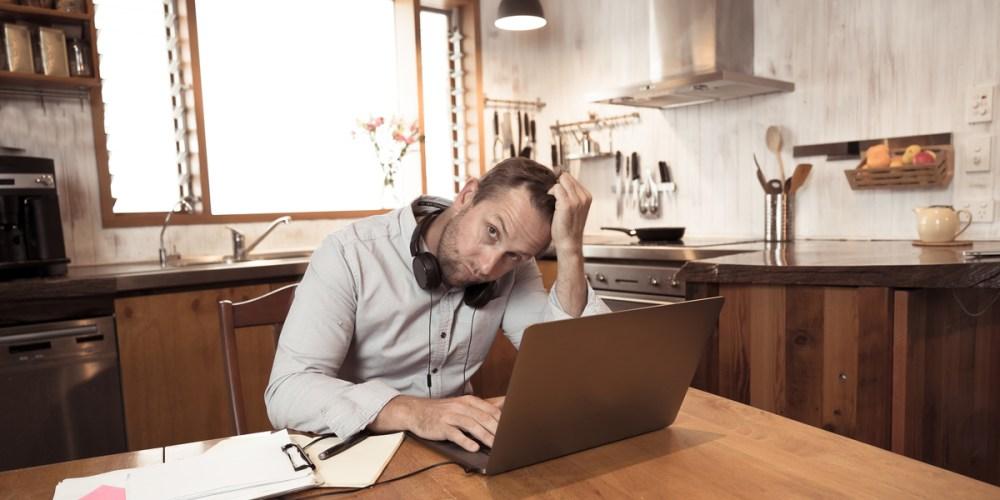 Man with headphones frustrated with poor audio in online meeting