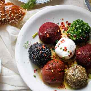 Coated in a selection of spices, seeds and nuts, homemade labaneh balls hide within them a perfectly creamy and tangy centre. A great vegetarian and gluten-free appetizer for a party, or as part of a breakfast spread.