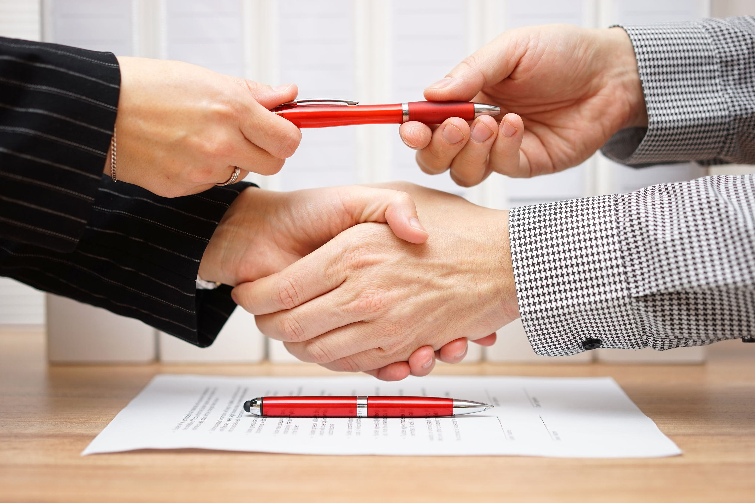 Business partners shaking hands and exchanging pen after finishe