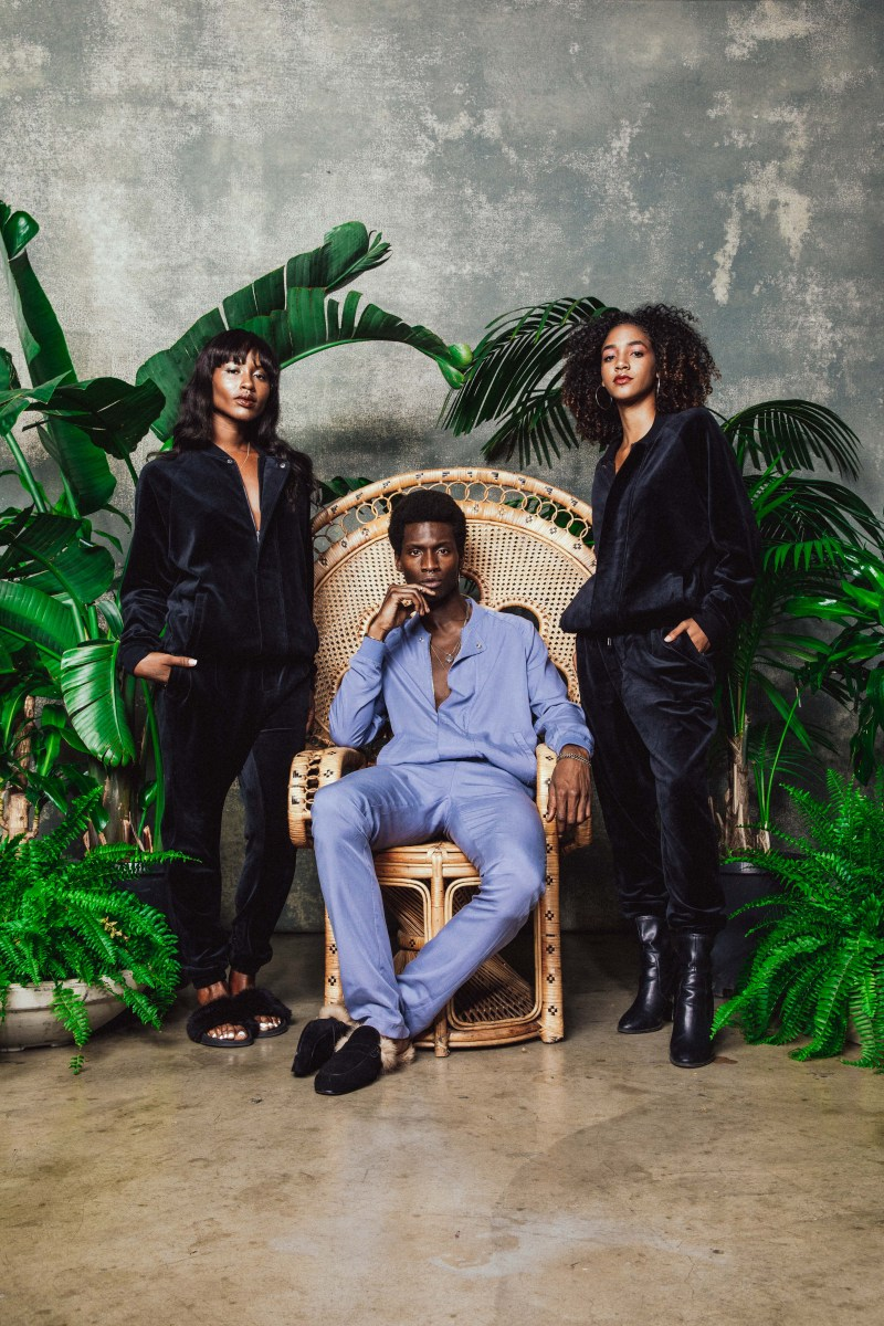 Bosso, clad in a cornflower blue track suit, sits in a wicker chair, surrounded by female models and tropical foliage.