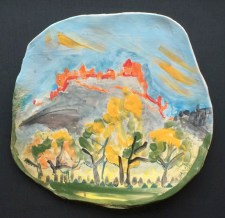 Pottery slab pressed into a wavy plate or art piece for display, with painted pattern of a view of Edinburgh castle from Princes Street.