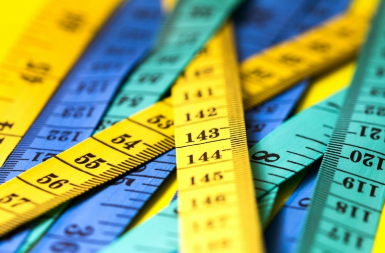 close up of several tape measures that are yellow, blue and turquoise