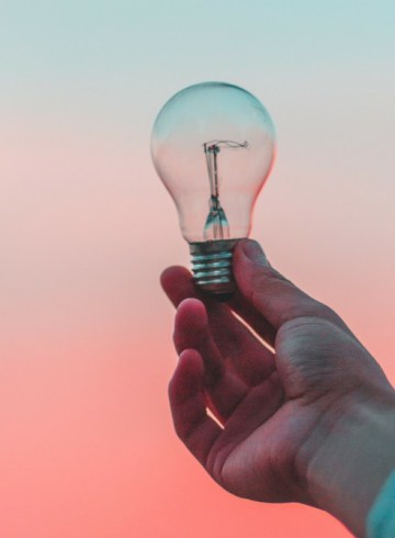 a hand holding an unlit light bulb against a blue and pink sunset