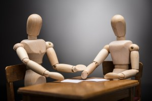 two wooden figures sat at a table with sheets of paper