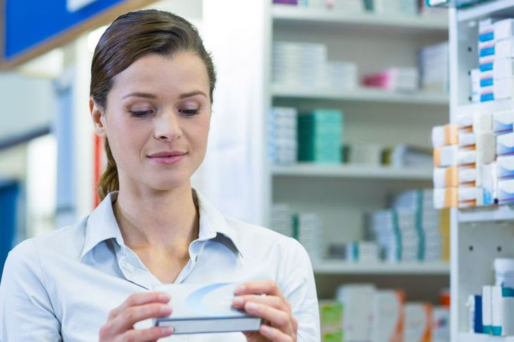 woman reading drug box in pharmacy