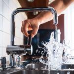 hand turning kitchen tap on