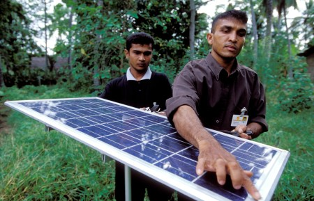 Two people install a solar panel to help light their village