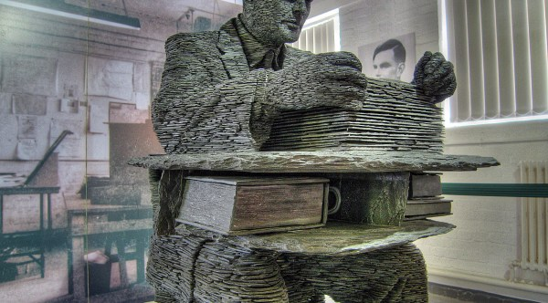 A statue of Alan Turing made from many layers of slate on show at Bletchley Park