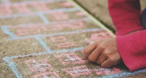 Child drawing a hopscotch in chalk on a playground floor