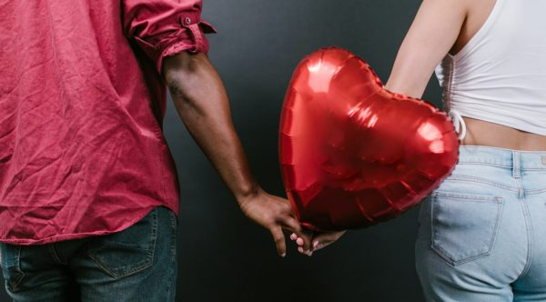 Two people holding hands with a heart-shaped balloon between them