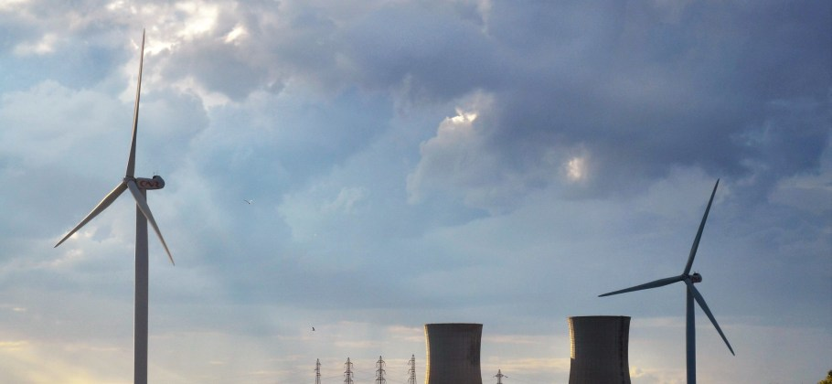 Powerlines in the background, nuclear cooling towers in the middle, and wind turnbines in the foreground. Set against a cloudy sky.