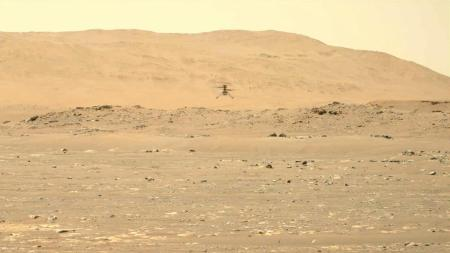 Photograph of the Ingenuity helicopter flying about 5 m from the groun. The foreground and background are reddish and show the surface of Mars