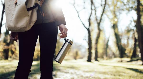 A forest with the back of a person in the foreground, holding a reusable water bottle
