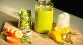 A green smoothie on a wooden chopping board surrounded by fruits and vegetables