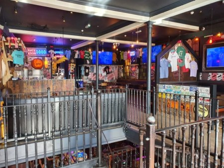 A room centred around a black staircase with Americana, including baseball shirts and beer posters, on the wall