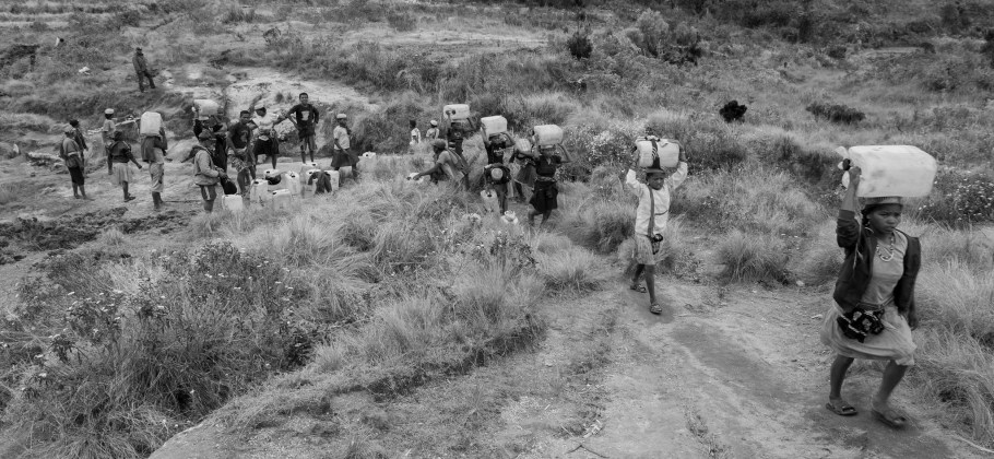 Black and white photo of people go to the market with barrels of alcohol and then come back with goods