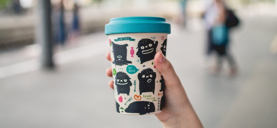 Photo of a person holding up a reusable cup