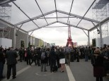 Journalists and negotiators gather around a large action beneath the Eiffel Tower
